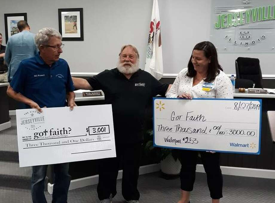 Steve Pegram, founder/president of Got Faith?, is shown with oversized checks representing gifts of $6,000. At left is Jerseyville Mayor Bill Russell; at right is Walmart Jerseyville manager Megan Labrena.