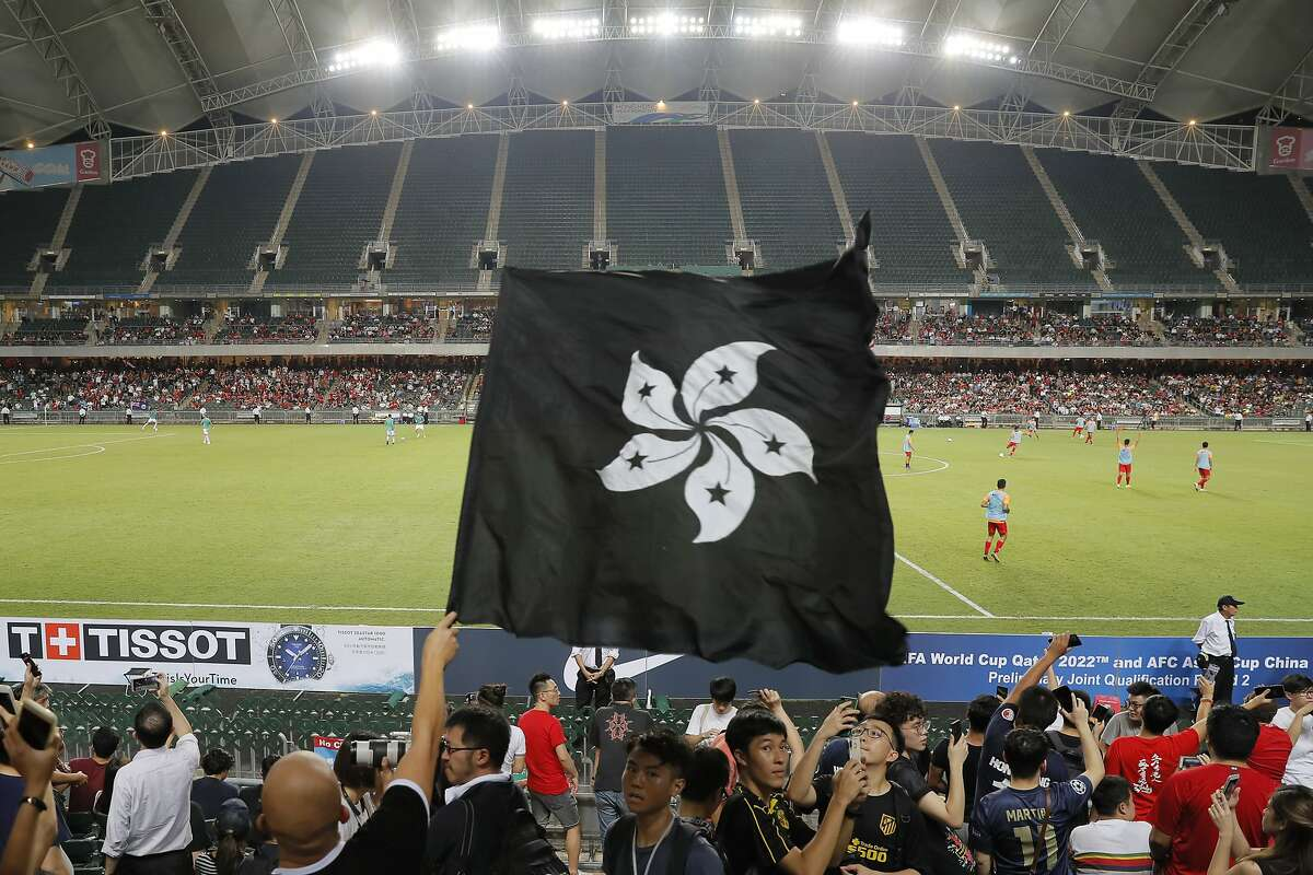 Hong Kong soccer fans waves a black version of the Hong Kong flag to protest against government during the FIFA World Cup Qatar 2022 and AFC Asian Cup 2023 Preliminary Joint Qualification Round 2 soccer match between Hong Kong and Iran, in Hong Kong, Tuesday, Sept. 10, 2019. The crowd broke out into