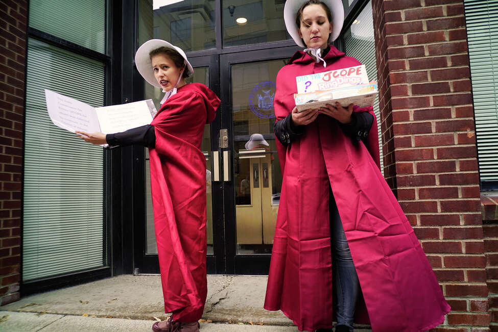 Two women dressed as characters from The Handmaid's Tale and supporters of Kat Sullivan, a former Emma Willard student and alleged rape victim, take part in an event outside the office of the New York State Joint Commission on Public Ethics on Tuesday, Sept. 10, 2019, in Albany, N.Y. JCOPE is pursuing Sullivan for alleged violations of lobbying regulations. (Paul Buckowski/Times)