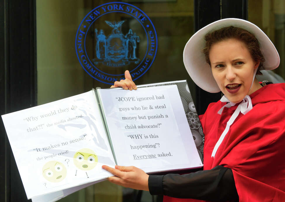 A woman dressed as a character from The Handmaid's Tale and a supporter of Kat Sullivan, a former Emma Willard student and alleged rape victim, takes part in an event outside the New York State Joint Commission on Public Ethics on Tuesday, Sept. 10, 2019, in Albany, N.Y. JCOPE is pursuing Sullivan for alleged violations of lobbying regulations. (Paul Buckowski/Times)