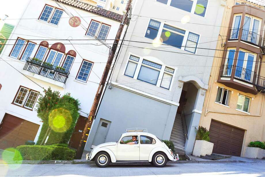 Ben Ramirez drives around San Francisco (hills and all) in his 1966 VW Beetle.  Yes, it's a manual. Photo: Blair Heagerty / SFGate