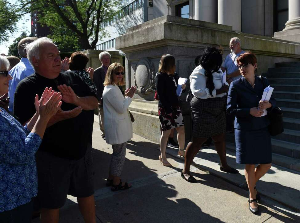 Attorney Victoria Esposito, advocacy coordinator for the Legal Aid Society of Northeastern New York, right, walks to the Schenectady County Judicial Building to file legal papers on behalf of St. Clare's pensioners against the Roman Catholic Diocese of Albany on Tuesday, Sept. 10, 2019, in Schenectady, N.Y. Her, and fellow attorneys joining the suit, were applauded by pensioners and family members, left, (Will Waldron/Times Union)