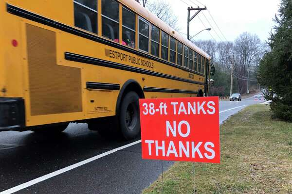 A school bus passes an anti-Aquarion tank sign in Westport in 2017.