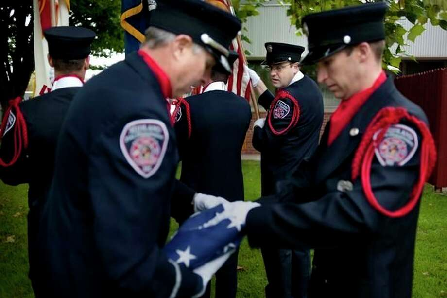 Midland Fire Department firetruck operator Chris Lince watches Lt. Greg Grobbel, left, and firefighter Phil Hepworth tuck in the edges of the American flag before raising it to half mast during a remembrance ceremony Sept. 11, 2015 for the 2,996 lives lost on Sept. 11, 2001. These lives included 343 firefighters, 72 law enforcement officers, and 55 military personnel. (Brittney Lohmiller/Daily News file)