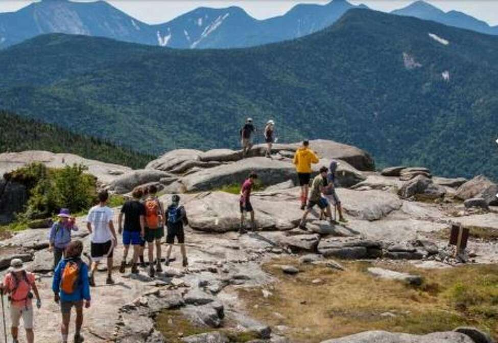 Hikers stand on the summit of Cascade Mountain on July 20, 2016
