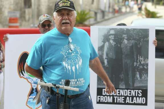 Raymond Hernandez points at a photo of his grandfather during a news conference Tuesday in front of the federal building across the street from the Alamo. At the news conference, it was announced that Tap Pilam Coahuiltecan Nation, the San Antonio Missions Cemetery Association and Hernandez filed suit against the city of San Antonio, the Texas General Land Office and two other parties to ensure lineal descendants rights are protected and regulatory processes are followed during the ongoing public-private Alamo renovation.
