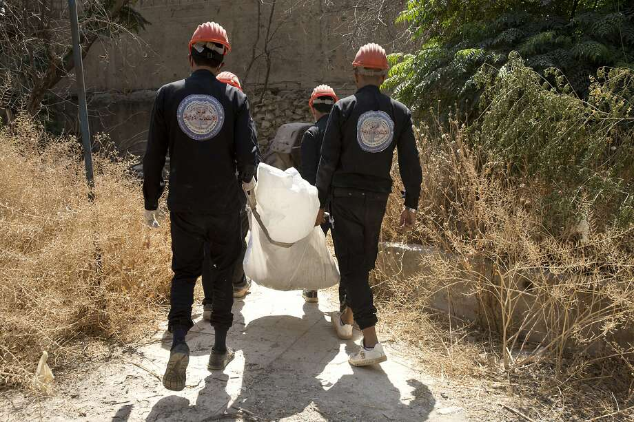 First responders said they have pulled nearly 20 bodies out of the latest mass grave uncovered in Raqqa. Photo: Maya Alleruzzo / Associated Press