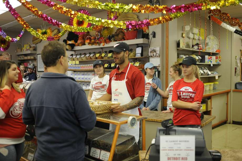Detroit Red Wings forward Andreas Athanasiou greets fans while working behind the counter with three teammates at St. Laurent Brothers in downtown Bay City on Tuesday, Sept. 10, 2019 as part of the Hockeytown Cares Community Tour. (Dan Chalk/chalk@mdn.net) Photo: Dan Chalk/chalk@mdn.net
