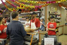 Detroit Red Wings forward Andreas Athanasiou greets fans while working behind the counter with three teammates at St. Laurent Brothers in downtown Bay City on Tuesday morning as part of the Hockeytown Cares Community Tour.