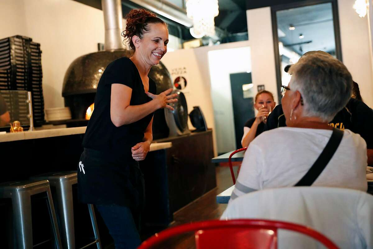 Server Penny Freeman signs with a customer at Mozzeria in San Francisco, Calif., on Sunday, September 8, 2019.