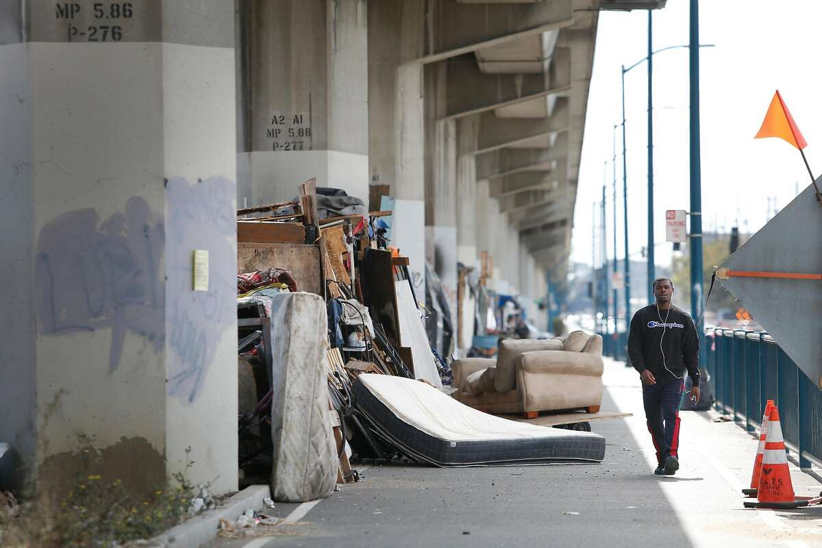 Joevaughn Norris of Oakland walks past makeshift structures people built and live in along San Leandro Avenue on Friday, September 6, 2019 in Oakland, CA. Oakland Public Works Department is requiring structures in a homeless encampment along San Leandro Avenue to be dissembled and removed by September 11, 2019 when the encampment will be temporarily closed for a full cleaning.