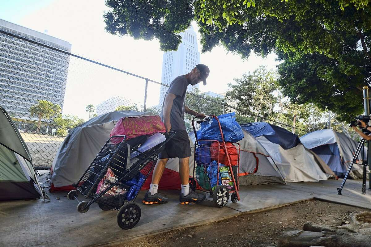 A homeless man moves his belongings from a street near Los Angeles City Hall as crews prepared to clean the area.