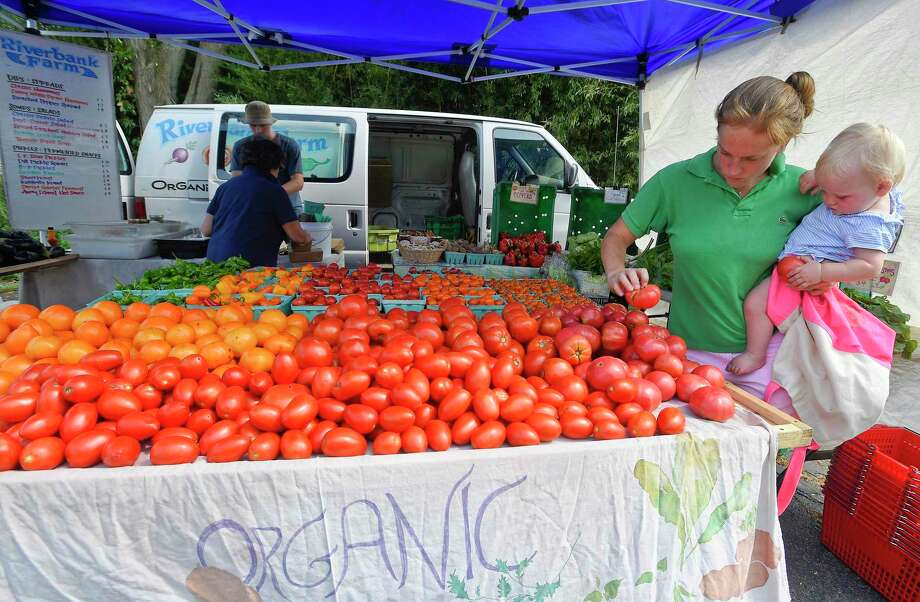 At right, Molly Otocka of Riverside, picks out tomatoes with her 13-month-old daughter Abigail while shopping for fresh produce from Riverbank Farms, one of several vendors set up at the Old Greenwich Farmers Market on Sept. 4, 2019. The farmers market is held every Wednesday, Rain or Shine, from 2:30 to 6 p.m. in the parking lot at Living Hope Community Church at 38 West End Avenue in Old Greenwich. Photo: Matthew Brown / Hearst Connecticut Media / Stamford Advocate