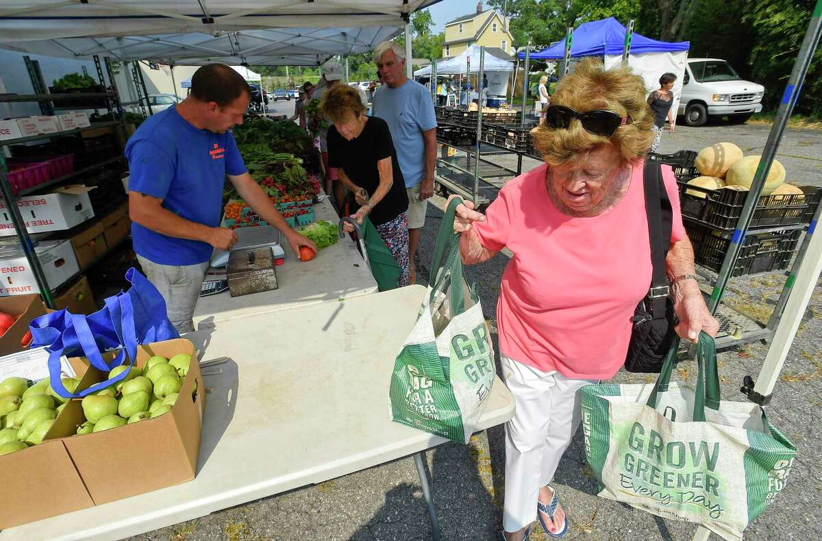Penny Monahan of Greenwich grabs her bags of fresh produce she purchased from Smith Acres Farm, one of several vendors set up at the Old Greenwich Farmers Market on Sept. 4, 2019. The farmers market is held every Wednesday, Rain or Shine, from 2:30 to 6 p.m. in the parking lot at Living Hope Community Church at 38 West End Avenue in Old Greenwich.