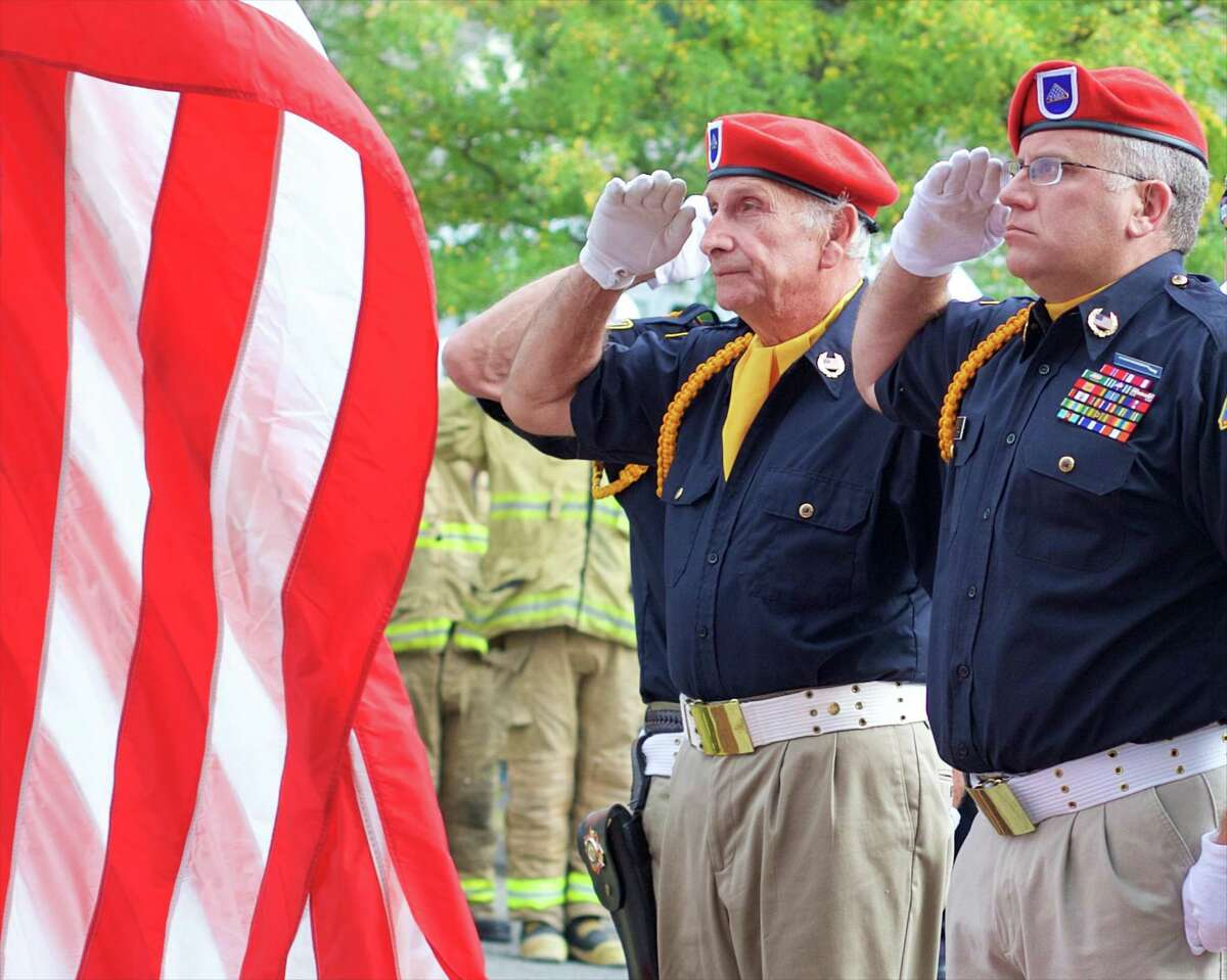 John Avalone (US Marine) and Robert Hill (US Army) salute as the new flag is raised during Sunday mornings 9/11 memorial ceremony in New Milford, CT.