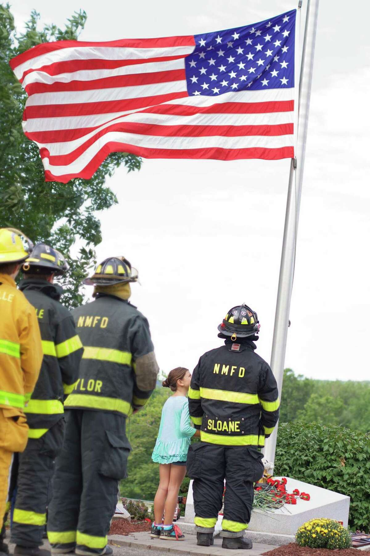 On Sunday, September 11, 2016, New Milford held a 9/11 Memorial Ceremony at the town's memorial on Patriot's Way. Tom Sloane from the New Milford Fire Department and Jillian Sloane (age 7) place flowers at the monument base at the end of the ceremony.