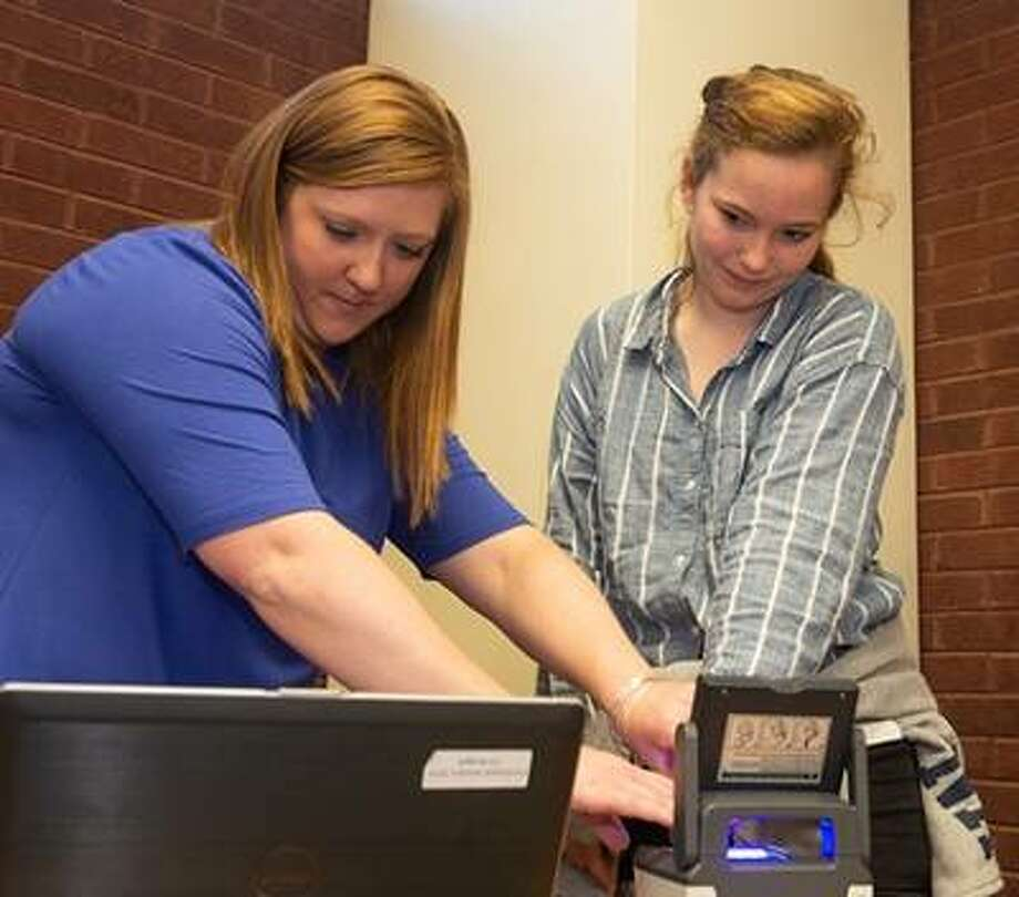 Heather Frank, with the Regional Office of Education, takes the finger prints of senior psychology major Sarah Love, who signed up to become a Give 30 mentor. Photo: Submitted