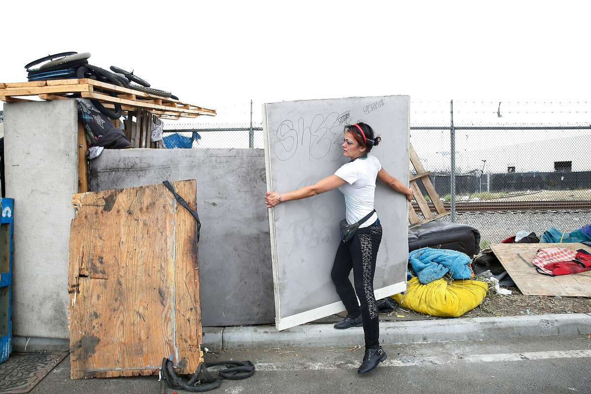 Jamie Dong carries materials from one person's site, who she said passed away, to the makeshift structure she lives in along San Leandro Avenue on Friday, September 6, 2019 in Oakland, CA.