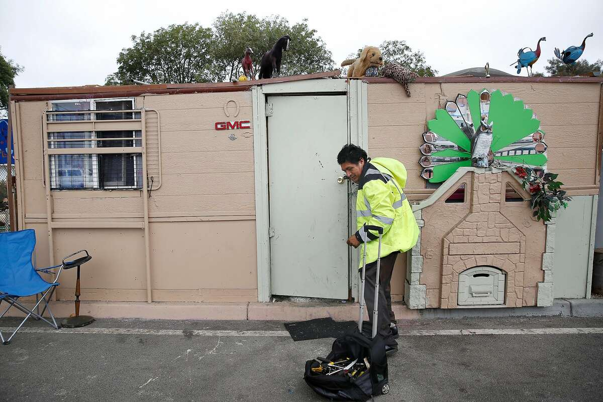 Pastor walks out the front of the structure he built and lives in along San Leandro Avenue as he heads off to his work in Oakland, CA.
