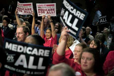 "Supporters of Sen. Bernie Sanders, I-Vt., hold signs as he speaks about his ""Medicare for All"" bill at a news conference in Washington on Sept. 13, 2017. The Vermont senator has staked his presidential campaign, and much of his political legacy, on transforming health care in America."