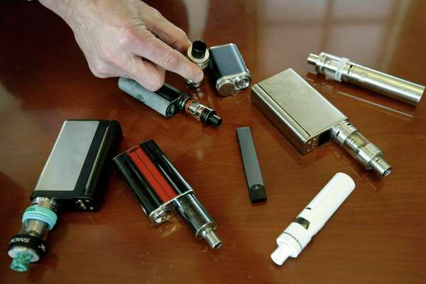FILE - In this April 10, 2018, file photo, a high school principal displays vaping devices that were confiscated from students in such places as restrooms or hallways at the school in Massachusetts. On Wednesday, April 3, 2019, the U.S. Food and Drug Administration said it has not established a direct connection between vaping and seizures but is seeking more information. Regulators noted that seizures and convulsions are a known side effect of nicotine poisoning. (AP Photo/Steven Senne, File)