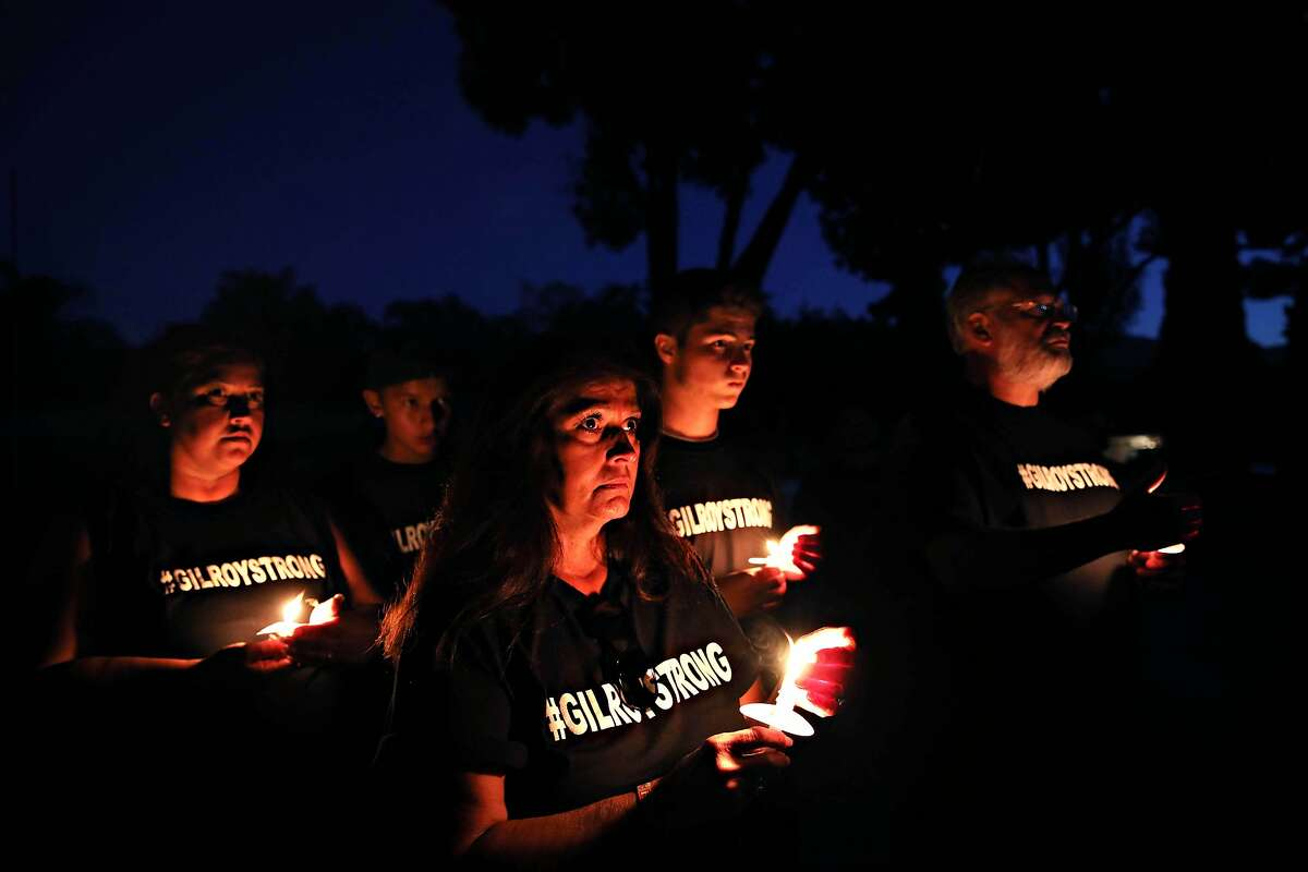 Liz Pieteroniski, third from left, stands with her daughter, Kimberly Farley, grandson Ryan Farley, 13, grandson, Ritchie Farley, 16, and husband Glenn Pieteroniski, during a candlelight vigil at El Roble Park in Gilroy, Calif., on Tuesday, July 30, 2019. The event, hosted by Idle Hands Studio and Gilroy Gold, was held two days following a mass shooting during the Gilroy Garlic Festival. Liz Pieteroniski left Christmas Hill Park thirty minutes before the shooting began.