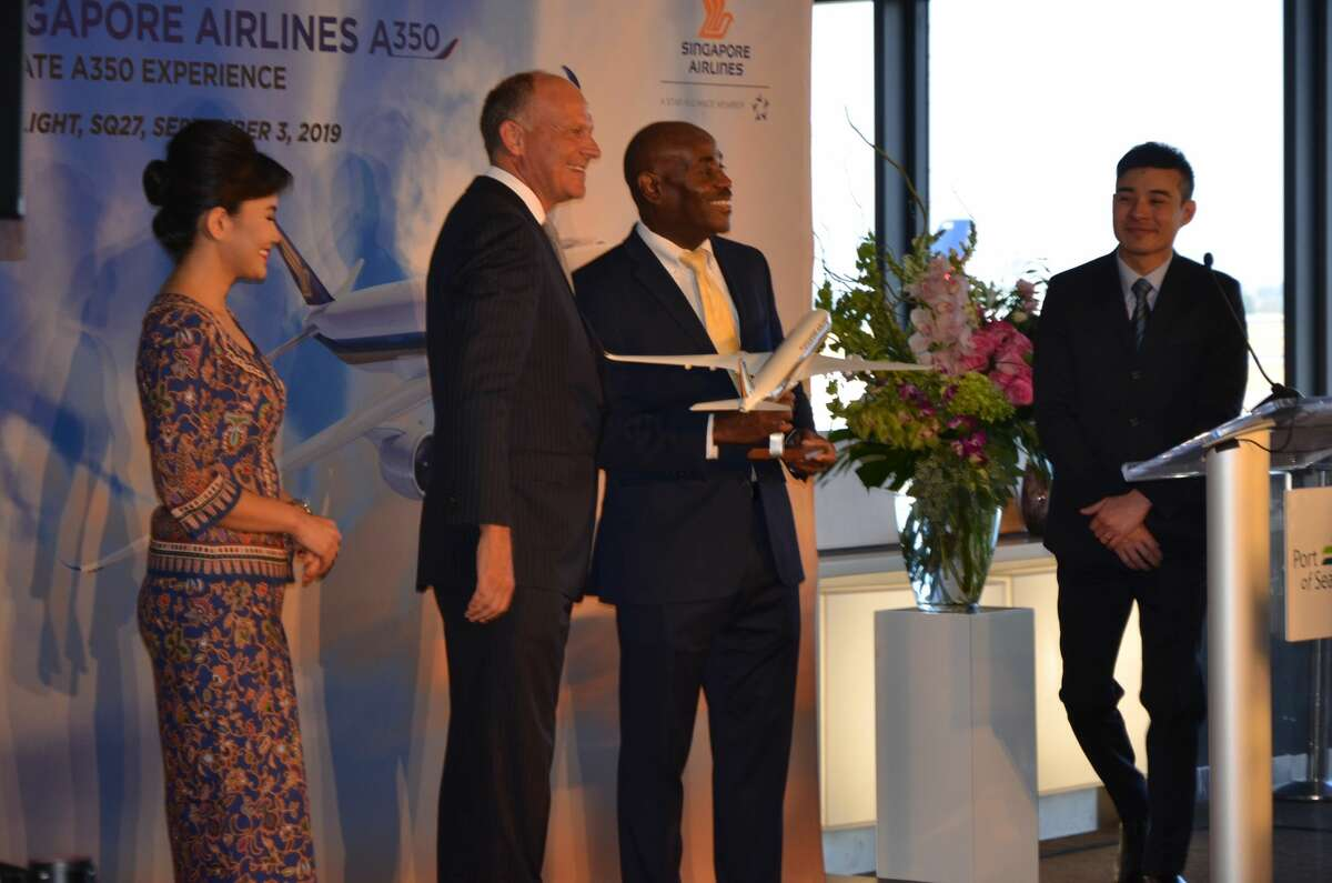 Singapore Airlines Senior Vice President of Sales & Marketing Campbell Wilson (left) presents Port of Seattle Airport Director Lance Lyttle with a model of the SQ A350.