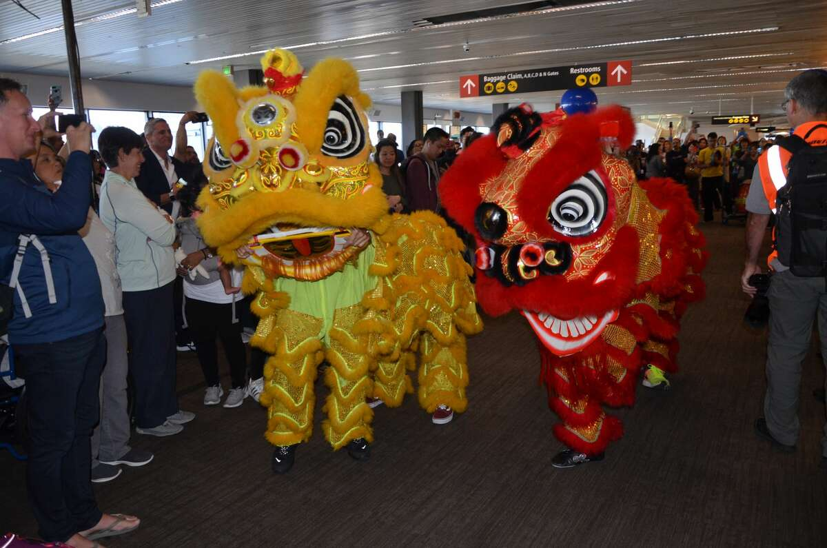 Lion dancers and lots of drumming take over Seattle-Tacoma's South Satellite Terminal to celebrate the launch of Singapore Airlines's first flight to Changi Airport.