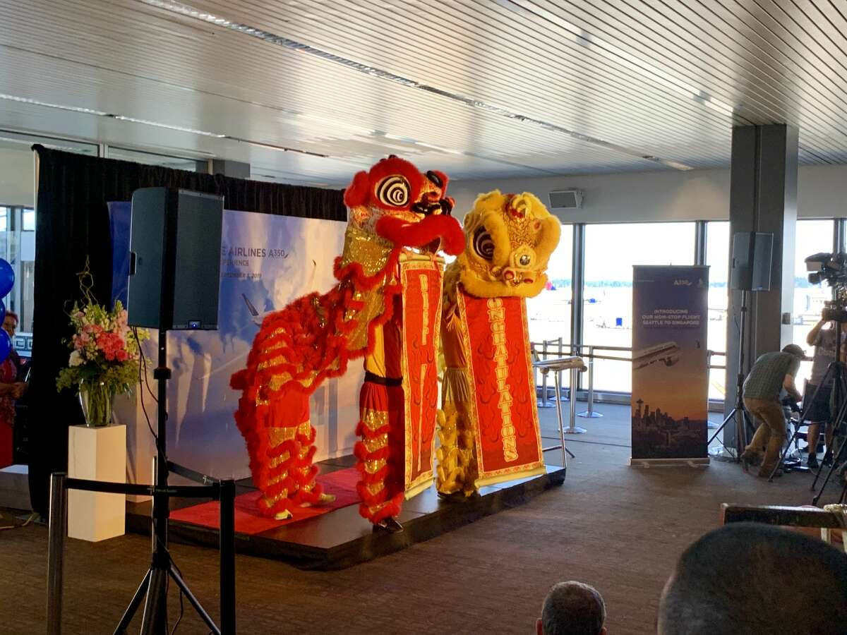 Lion dancers unfurl 'Best Wishes' and 'Congratulations' signs at the gate celebration for the Singapore Airlines flight launch.