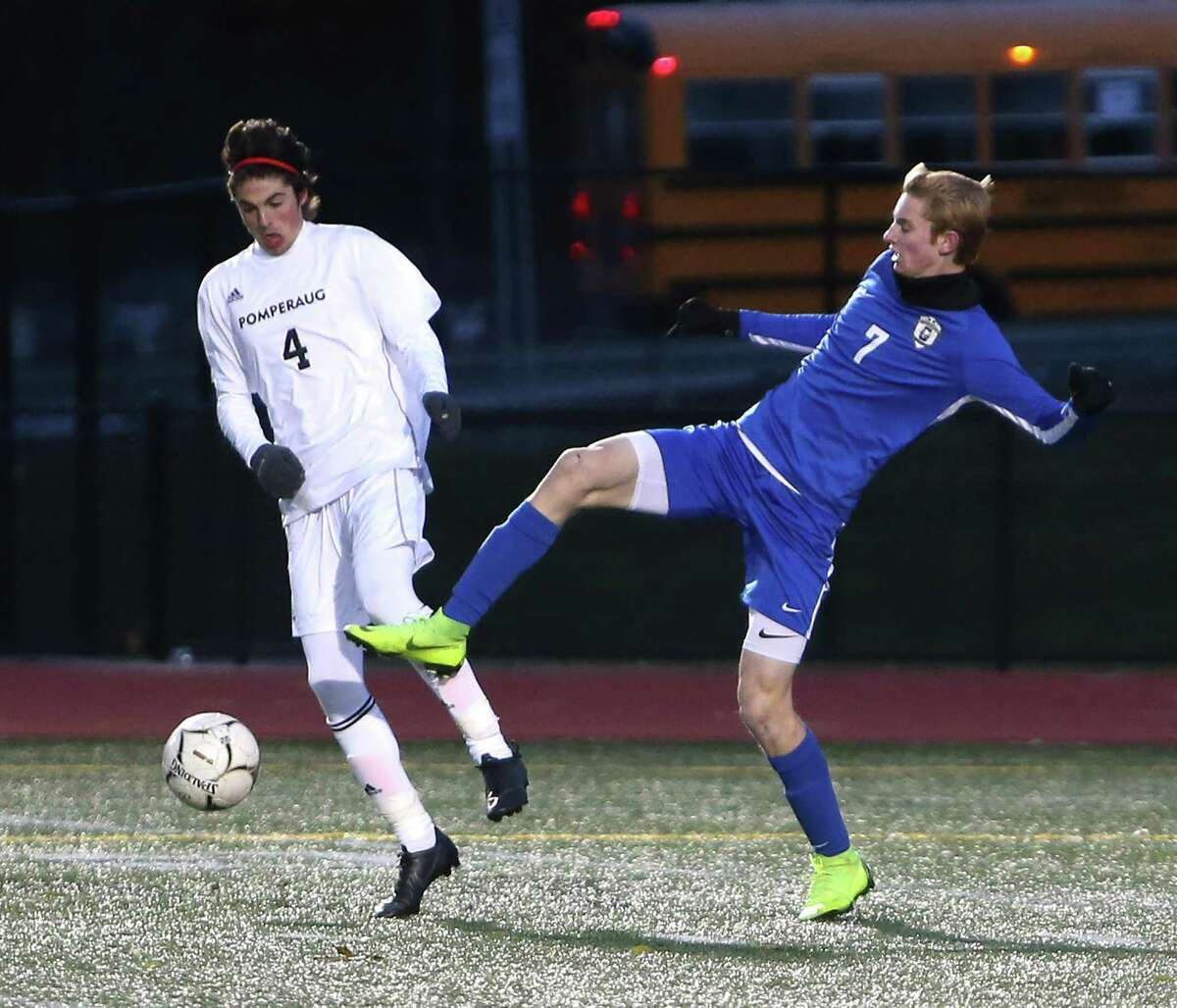 Glastonbury High School's Alec Hughes battles Pomperaug High School's Harrison McQuillan for the ball during the Class LL boys soccer semifinals in New Britain on Wednesday, Nov. 14, 2018.