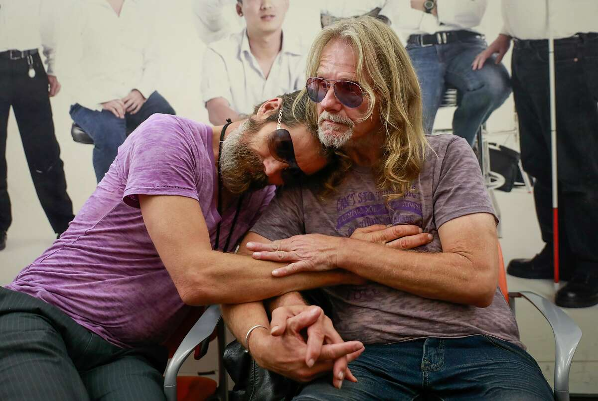 Robert Fleischaur and partner Rickey Lee (right) embrace at Ward 86 as they wait for an appointment at the Zuckerberg San Francisco Hospital in San Francisco, California, on Tuesday, Sept. 10, 2019. They both have HIV.