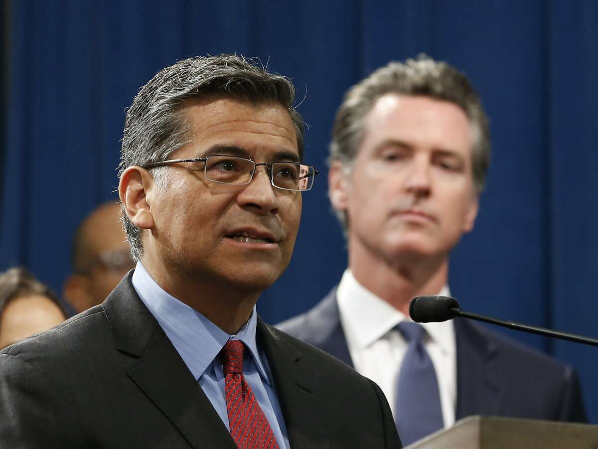 FILE -- In this Aug. 16, 2019 file photo California Attorney General Xavier Becerra, left, accompanied by Gov. Gavin Newsom, addresses reporters at a news conference in Sacramento, Calif. Becerra argued in a Thursday, Sept. 5, 2019 court filing that a new law requiring presidential candidates to release their tax returns doesn't bar anyone from accessing the ballot. The Trump campaign is trying to block the new law from taking effect. (AP Photo/Rich Pedroncelli, File)