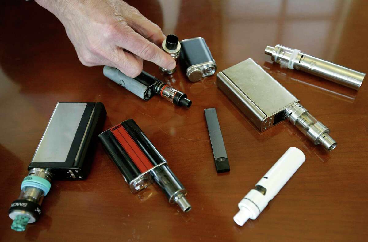 In this file photo, a Marshfield, Mass., high school principal displays vaping devices that were confiscated from students in such places as restrooms or hallways at the school.