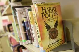 """Harry Potter and the Cursed Child,"" one of this summer's most popular books, sits on the returns shelf at Greenwich Library in Greenwich, Conn. Thursday, Aug. 18, 2016."