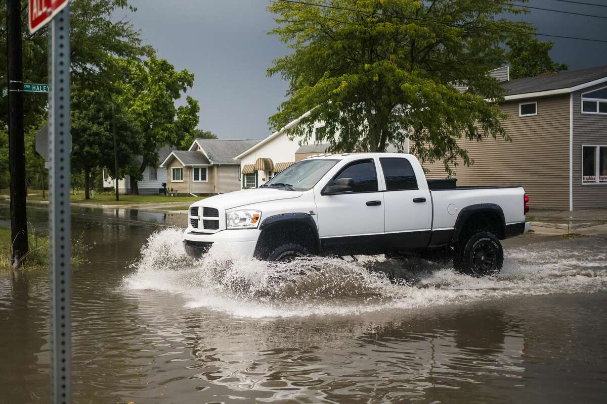Cars drive through floodwater at the intersection of Haley and Carpenter Streets after a thunderstorm Tuesday, Sept. 10, 2019 in Midland. (Katy Kildee/kkildee@mdn.net)