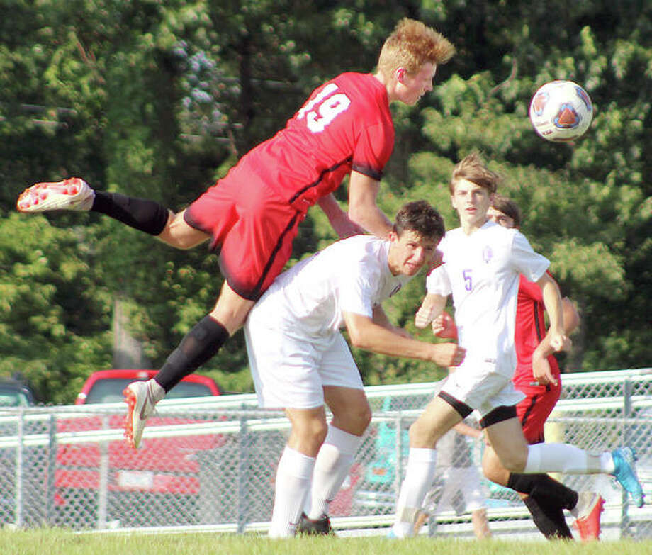 Alton's Braden Schrimpf (19) goes over the back of Collinsville's Anthony Coppotelli to head the ball during Tuesday's soccer game at Alton High. Coppotelli had the assist on teammate Ryan Null's goal in the Kahoks' 1-0 Southwestern Conference victory. Photo: Pete Hayes | The Telegraph