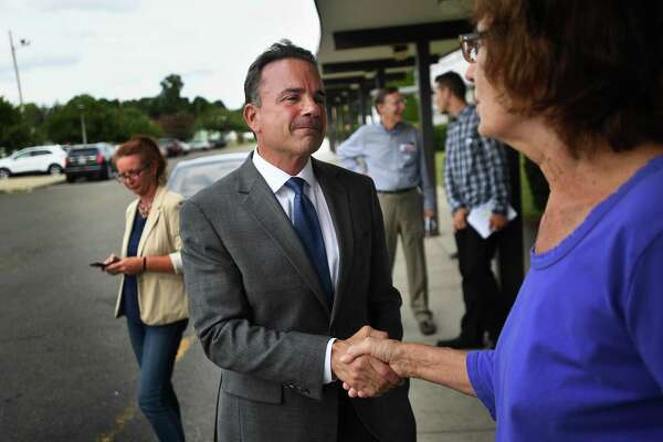 Bridgeport Mayor Joe Ganim greets voter Catherine Zahorsky outside Blackham School during the Bridgeport primary on Monday. He is one of seven white males likely to be running the state's largest cities after the November election.