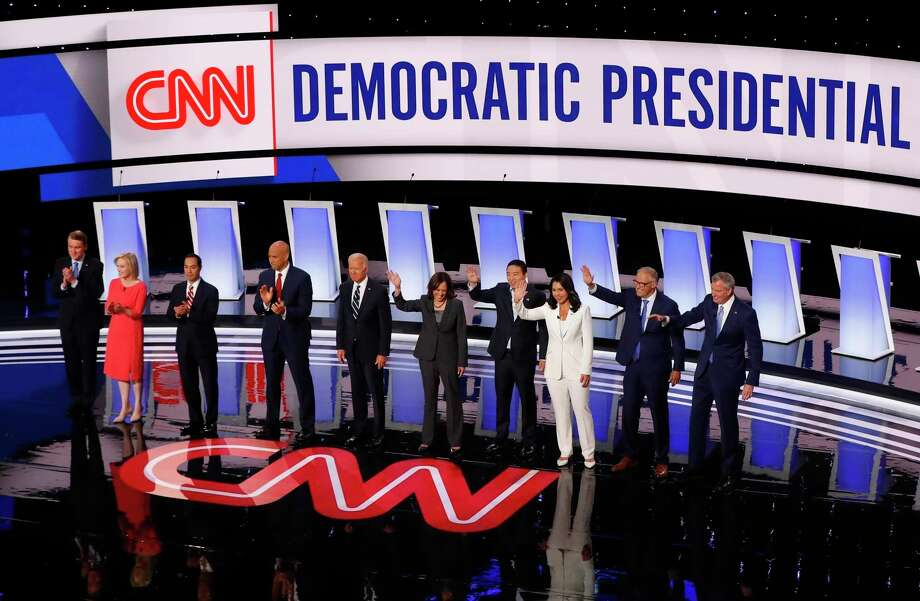 FILE - In this July 31, 2019 file photo, Sen. Michael Bennet, D-Colo., Sen. Kirsten Gillibrand, D-N.Y., former Housing and Urban Development Secretary Julian Castro, Sen. Cory Booker, D-N.J., former Vice President Joe Biden, Sen. Kamala Harris, D-Calif., Andrew Yang, Rep. Tulsi Gabbard, D-Hawaii, Washington Gov. Jay Inslee and New York City Mayor Bill de Blasio are introduced before the second of two Democratic presidential primary debates hosted by CNN in the Fox Theatre in Detroit. (AP Photo/Paul Sancya) Photo: Paul Sancya, STF / Associated Press / Copyright 2019 The Associated Press. All rights reserved.