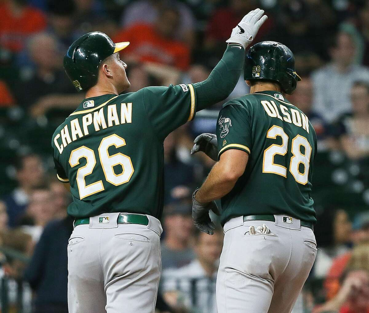 HOUSTON, TEXAS - SEPTEMBER 10: Matt Chapman #26 of the Oakland Athletics taps Matt Olson #28 on his head after Olson hit a home run in the fourth inning against the Houston Astros at Minute Maid Park on September 10, 2019 in Houston, Texas. (Photo by Bob Levey/Getty Images)