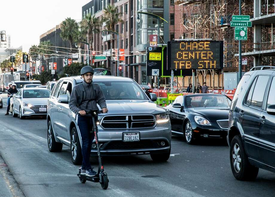 A sign directs drivers toward Chase Center as cars slowly creep up 3rd Street looking for parking  on a night with the Dave Matthews Band playing the new Warriors arena and Giants toiling at Oracle Park. Photo: Jessica Christian / The Chronicle