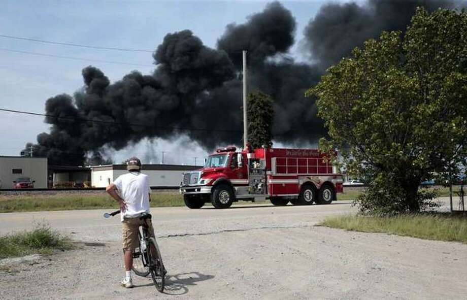 A resident watches as a firetruck arrives in downtown Dupo, Ill. to help fight a tanker fire from a derailed train on Tuesday. Black smoke coming from the derailment scene can be seen for miles and caused the evacuation of schools in the town, authorities said. (Robert Cohen/St. Louis Post-Dispatch via AP)