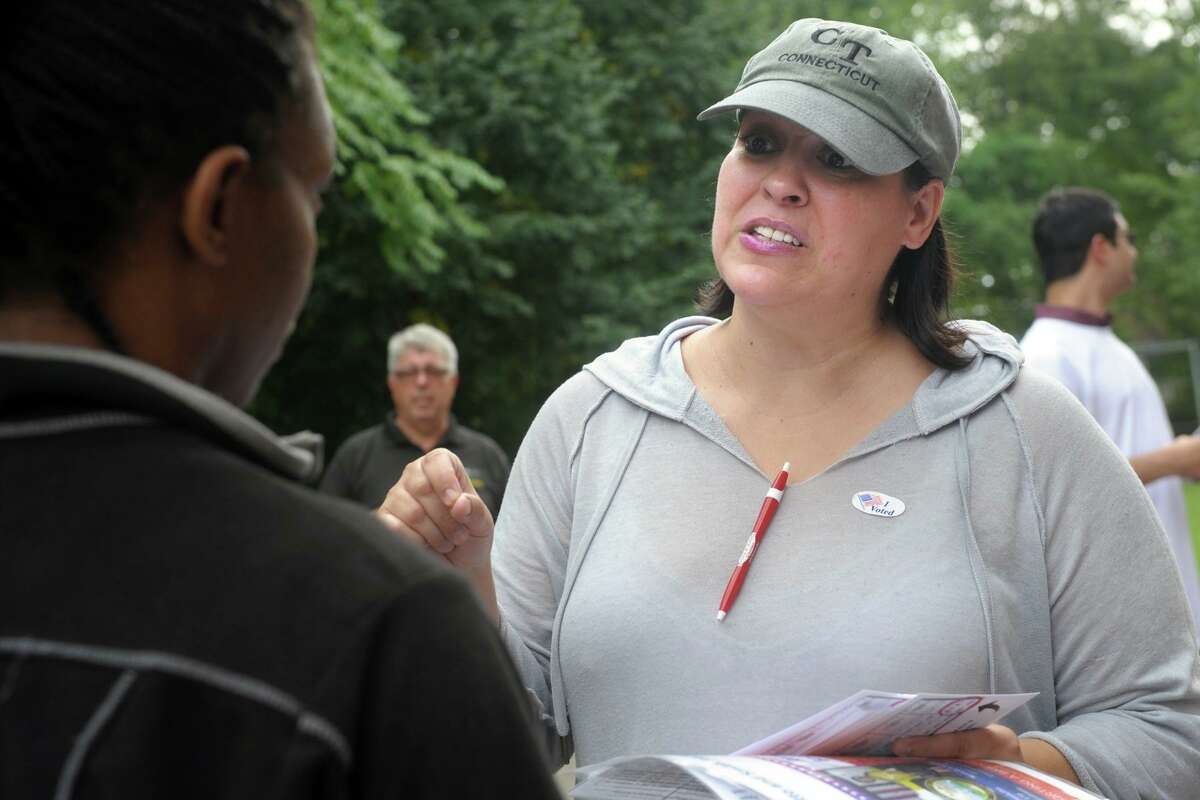 Maria Pereira, a democratic petition candidate for Bridgeport's City Council seat in the 138th District, greets voters arriving to vote in Tuesday's primary elections at Thomas Hooker School, in Bridgeport, Conn. Sept. 10, 2019.