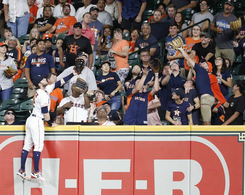 Houston Astros right fielder Josh Reddick (22) climbs up the wall as he tried to catch Oakland Athletics Marcus Semien's two-run home run during the fourth inning of a MLB baseball game at Minute Maid Park, Tuesday, Sept. 10, 2019, in Houston.