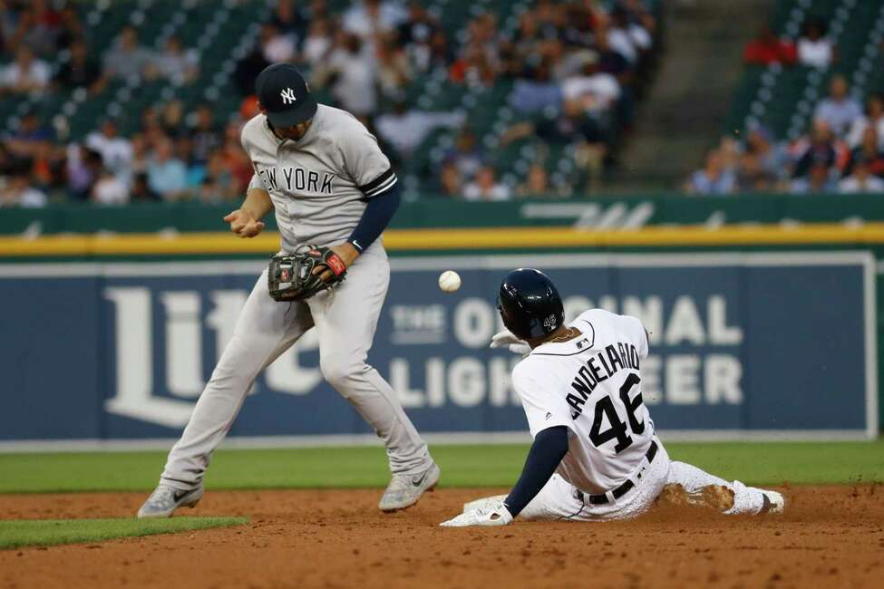 New York Yankees second baseman Gleyber Torres can't handle a throw as Detroit Tigers' Jeimer Candelario (46) slides into second base in the third inning of a baseball game in Detroit, Tuesday, Sept. 10, 2019. Torres was charged with an error on the play. (AP Photo/Paul Sancya)