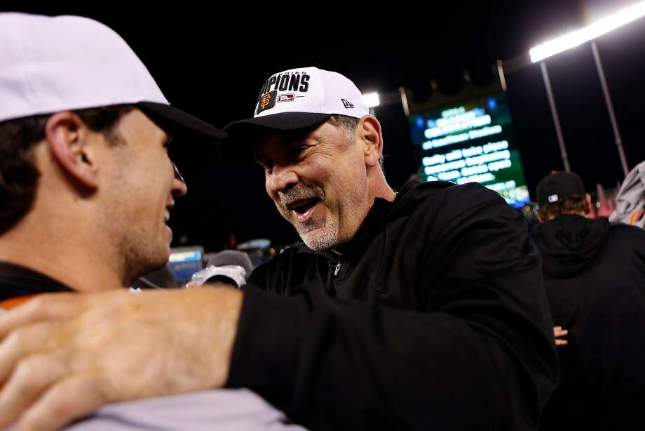 Giants' manager Bruce Bochy and Buster Posey celebrate a 3-2 win over the Kansas City Royals in Game 7 of the World Series at Kauffman Stadium on Oct. 29, 2014. Photo: Scott Strazzante / The Chronicle
