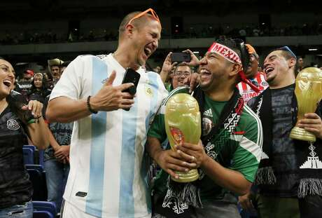 Soccer fans Diego Montoya, left, and Rafael Perez enjoy themselves before Mexico and Argentina take the field Tuesday.