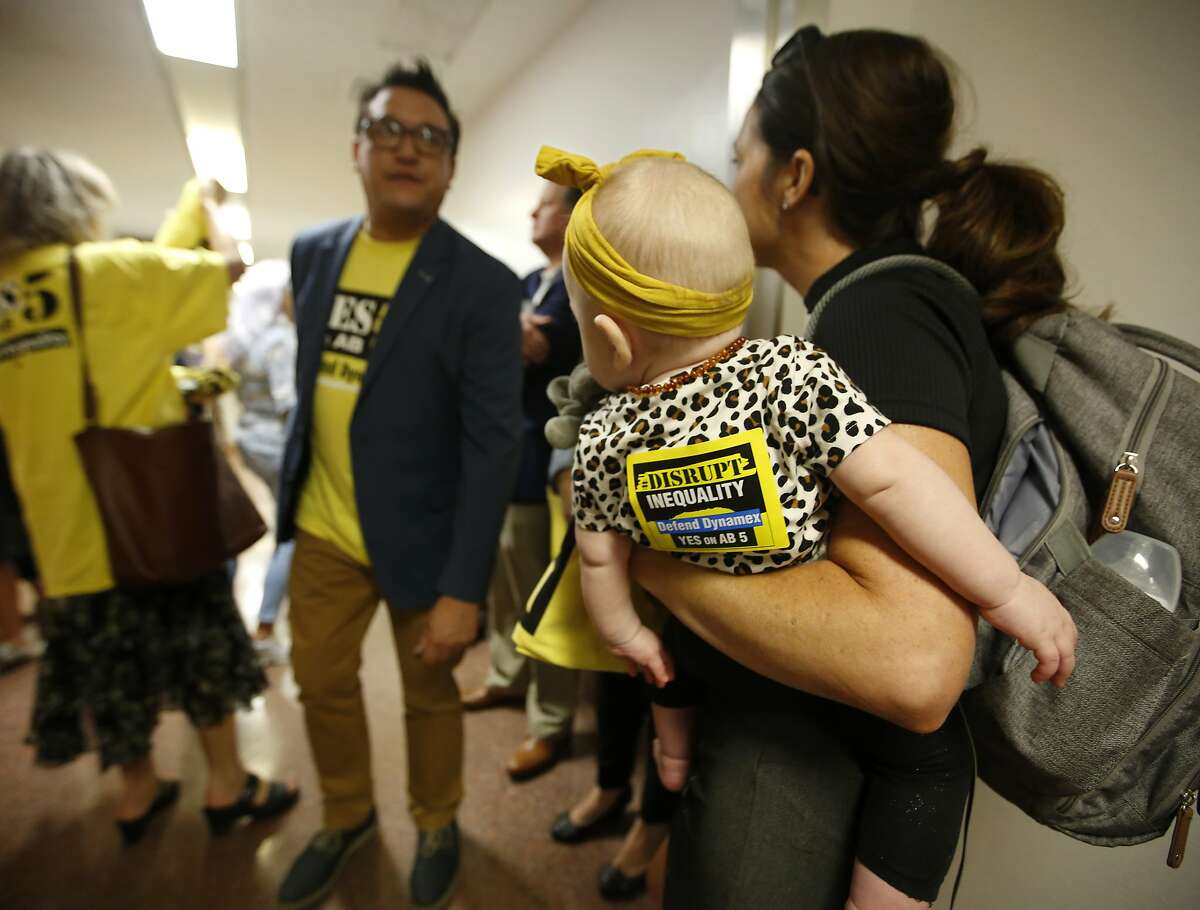 Nichole Rice holds her daughter, Goldie, 9 months, as she joins others advocating for the passage of AB5, a measure to limit when companies can label workers as independent contractors, at the Capitol in Sacramento, Calif., Tuesday, Sept. 10, 2019. Legislators have a Sept. 13 deadline to complete all business before the end of this year's legislative session. (AP Photo/Rich Pedroncelli)