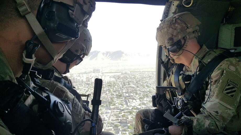 U.S. soldiers take in a view of Kabul, Afghanistan, on June 2, 2018, while flying over the city in a Black Hawk helicopter. Photo: Washington Post Photo By Dan Lamothe. / TWP