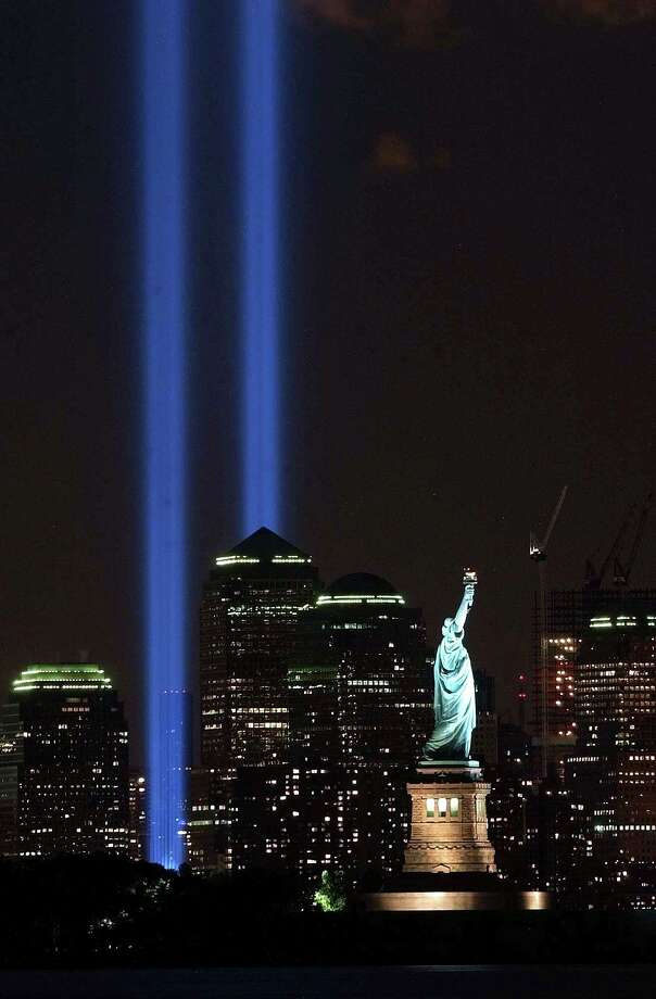 The Tribute in Light shines over the Manhattan skyline and the Statue of Liberty in New York on Sept. 11, 2004. Photo: Associated Press / AP2004