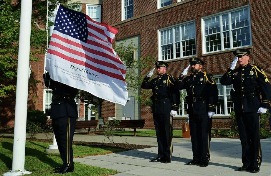 The Norwalk Police Department Honor Guard raises the new colors honoring the victims of September 11 2001 as The City of Norwalk holds a remembrance event to honor the 14 Norwalk residents who lost their lives during the September 11, 2001 attacks and all of the victims of 9-11 Wednesday, September 11, 2019, in Norwalk, Conn. . Photo: Erik Trautmann / Hearst Connecticut Media / Norwalk Hour